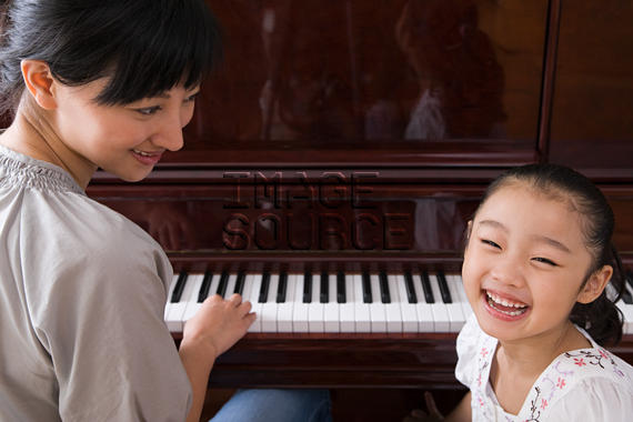A mother playing the piano for her daughter